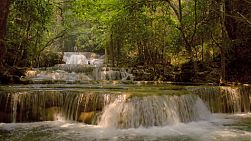 Water flowing down and cascading over various small waterfalls in the Huay Mae Khamin waterfalls in Kanchanaburi, Thailand. With people swimming and jumping off a waterfall in the background.