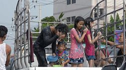 Bangkok, Thailand - April 14, 2014: Chidlren standing on the back of a truck getting splashed and sprayed with water during the water fights of the Songkran Festival in Thailand.