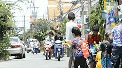 Bangkok, Thailand - April 13, 2012: Children enjoying the annual Songkran festivities with a water fight involving passing motorbikes.  Songkran is traditionally the Thai New Year, and as part of the celebrations, pouring water over other people is done as a way of blessing them. This has escalated to major water fights on the streets, with people pouring water on, or throwing water over anyone who passes by.  [binicons]293727 h 21 icon[/binicons]