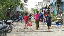 Young children walk through a slum community in the city of Phnom Pehn, Cambodia.