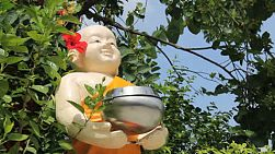 A chubby Buddhist state holds the donation bowl outside of the temple in Bangkok, Thailand.