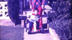 A chubby toddler enjoys riding his Big Wheel tricycle down the sidewalk while his loving Grandma watches in 1972.