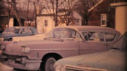 A man drives his Cadillac into a crowded snowy parking lot in the winter of 1963.