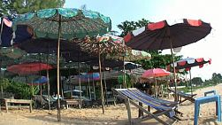 Colorful beach chairs wait for tourists on a beach near Sattahip, Thailand.