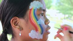 A cute 11 year old Asian girl gets a funky rainbow painted on her face.