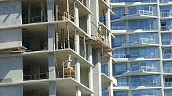 A group of construction workers are busy at work trying to finish off a new high rise building in downtown Vancouver, BC.