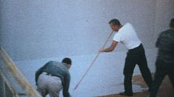 A group of hard working men paint the inside of a new in ground swimming pool in the summer of 1967.