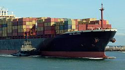 A loaded container ship with tugboat arriving into Fremantle Harbour in Western Australia.