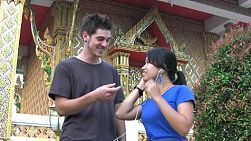 A young foreigner meets his Thai girlfriend outside the temple and lets her listen to his music in Bangkok, Thailand.
