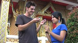 A young couple listen to music together while standing outside the temple in Bangkok, Thailand.