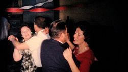Coworkers and employees enjoy the company staff Christmas party with food, live music and dancing in December 1963.