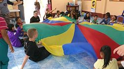 A group of high school students on a short term overseas missions trip have fun using a parachute with Thai children in Thailand.