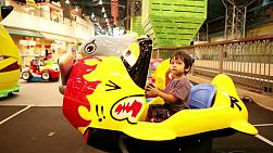 A cute little 2 year old Asian boy enjoys a fun airplane ride at the carnival in Bangkok, Thailand.