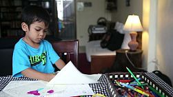 A cute Asian boy spends time coloring at his home in Bangkok, Thailand.