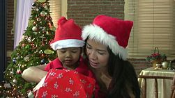 A loving Asian mother helps her beautiful young Thai boy open his Christmas present.