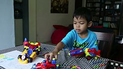 A cute little 4 year old Asian boy has fun playing with his toys after colouring a picture at home in Bangkok, Thailand.