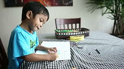 A cute little 4 year old Asian boy has fun colouring a picture at home in Bangkok, Thailand.
