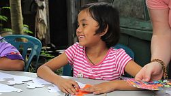 A cute female Asian girl in the slums diligently colors her coloring sheet during an English class in Bangkok, Thailand.
