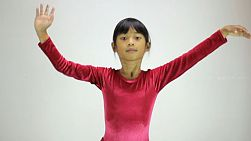 A cute little 7 year old Asian girl does a fun interpretive dance.