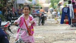 A cute little Khmer girl hangs out talking to her friends and sipping a cold drink in the slums of Phnom Pehn, Cambodia.