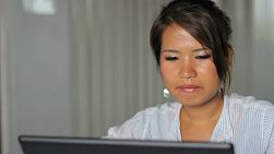 A pretty Asian girl pauses to listen to some music at the office.