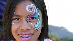 A cute Asian girl has fun getting her face painted at the local festival in the spring of 2015.