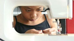 A cute Asian girl learning how to sew on her Mom's sewing machine.