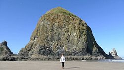 A cute little 11 year old Asian girl enjoys exploring Haystack Rock on Cannon Beach in Oregon.