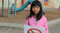 A cute Asian girl holds up a large NO BULLYING sign on the school playground.