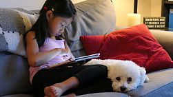 A cute little Asian girl uses her tablet alone in the living room at night with her faithful puppy at her side.