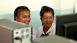 BURIRAM, THAILAND, SEPTEMBER 2013: Two cute Thai girls work together on the computer lab in school in Buriram, Thailand.