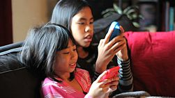 Two cute Asian sisters enjoy spending time together playing video games in the living room.