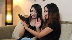 Attractive Asian women enjoy a fun phone call with their friend using their new PC digital tablet in Bangkok, Thailand.