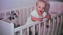A very happy little baby boy enjoys hanging out in his crib in 1964.