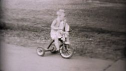 A cute little boy rides his new tricycle while he sucks his thumb in the summer of 1957.
