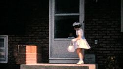 A cute little girl models her new Easter dress for the camera in front of her home in 1964.
