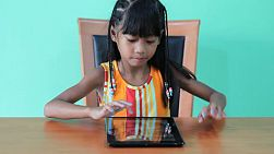 A cute seven year old Asian girl is excited to play games on her new digital tablet.