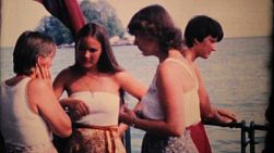 Cute young adult girls take a ferry to a remote tropical island in Thailand while on holidays in 1970.