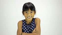 A cute little 7 year old Asian girl smiles at the camera.