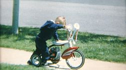 A cute little boy crashes his tricycle on the sidewalk in the summer of 1967.
