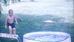 A cute little blond haired boy enjoys jumping and diving and splashing in his new kiddie pool in the back yard in 1967.