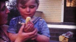 A cute little boy holds a baby chick for the first time ever with the help of his Mom in 1967.