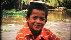 A cute little Thai boy joins the tourists as they explore Bangkok, Thailand on a classic canal boat tour in 1967.