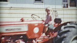 A cute little blonde girl has a blast pretending to drive her grandpa's big red tractor in the summer of 1966.