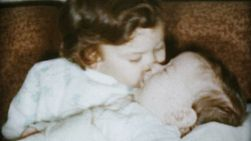 A very kind and caring older sister cuddles and kisses her brand new baby brother on Christmas Day in 1959.