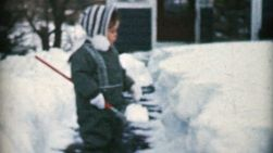 A cute little girl plays outside and helps to shovel the front sidewalk on a snowy winters day in December 1959.