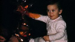 A cute little baby girl has fun opening up a special gift at Christmas in 1967.