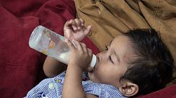 A cute little Asian toddler enjoys drinking his bottle and cuddling in Bangkok, Thailand.