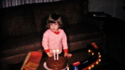 A cute little two year old girl blows out the candles on her birthday cake in 1961.
