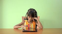 A young asian girl sitting at a table enjoying playing on her ipad.